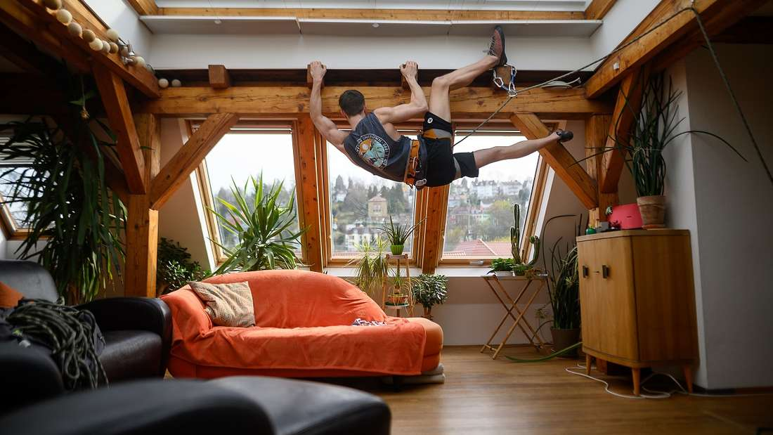 Not macht erfinderisch:Kletterer Niklas hängt zum Spaß in seiner Kletterausrüstung an einem Dachbalken im Wohnzimmer der Wohnung, in der seine Familie in Stuttgart wohnt. Um die Verbreitung des Coronavirus zu verlangsamen haben auch Kletterhallen geschlossen.