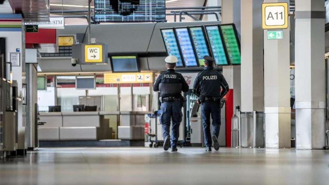 Polizisten patrouillieren am Flughafen Berlin-Tegel durch das Terminal. Foto: Michael Kappeler/dpa