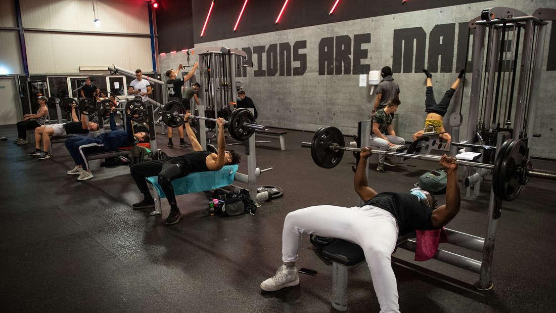 Männer trainieren in einem Fitnessstudio der Kette McFit an Langhantelbänken (Archivbild).