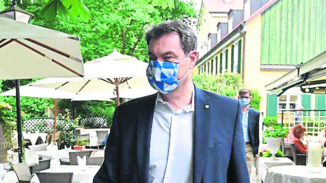Nur mit Maske darf sich Söder durch das Restaurant zum Tisch bewegen.
