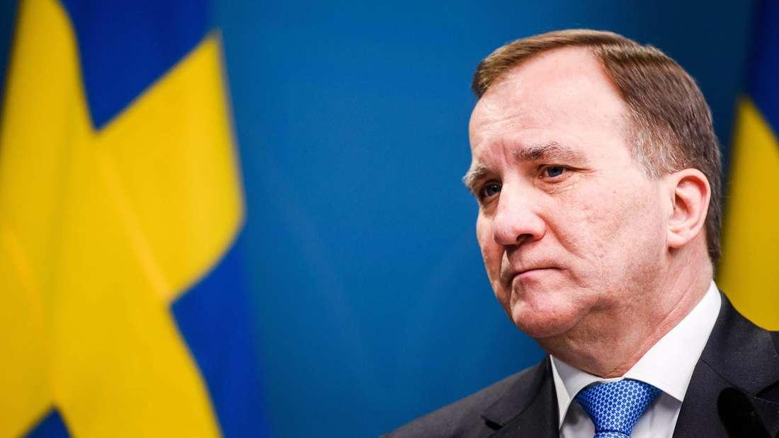 Stefan Löfven steht vor einer schwedischen Flagge.