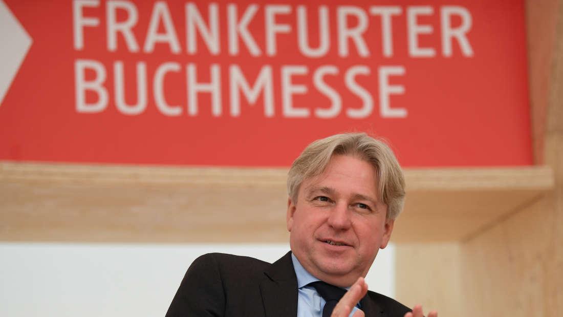 Veranstalter Juergen Boos sitzt vor einem Plakat der Frankfurter Buchmesse.