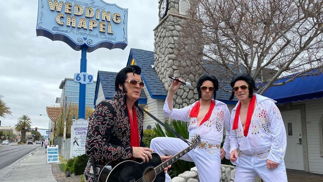 Ein Pfarrer, Oliver Pocher und sein Vater stehen vor einer Kapelle in Las Vegas. Alle drei sind als Elvis Presley verkleidet.