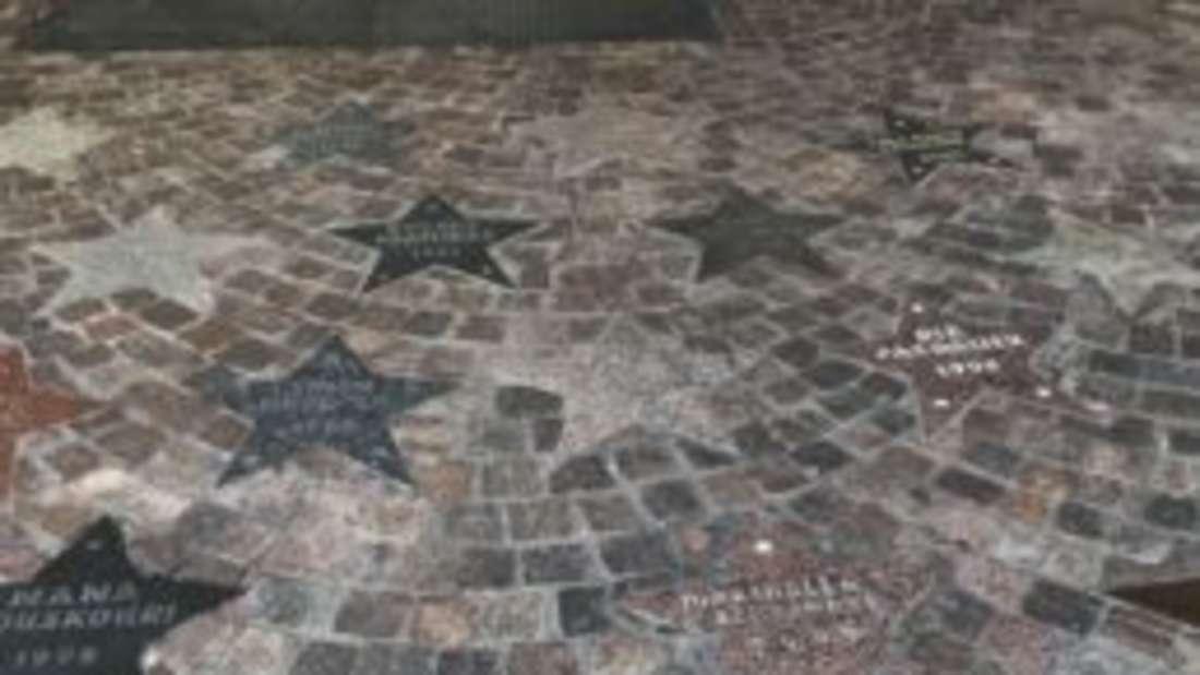 Vor der Tür einer Halle befinden sich mehrere Sterne im Boden. Diese zeigen Namen wie ZZ Top oder Xavier Naidoo und das Jahr, in dem sie dort aufgetreten sind.