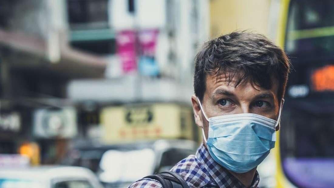Mann mit Maske und Rucksack auf einem belebten Platz in einer Großstadt.