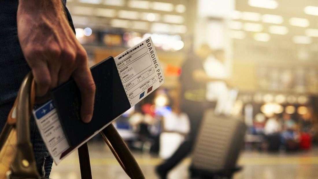 Eine Person steht am Flughafen und hält einen Reisepass und ein Flugticket in der Hand.
