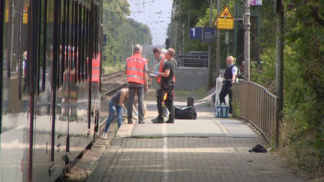 20.07.2019, Nordrhein-Westfalen, Voerde: Polizeibeamte suchen am Bahnhof in Voerde nach Spuren. Ein 28-jähriger Mann hat nach Polizeiangaben am Bahnhof im niederrheinischen Voerde eine 34-jährige Frau vom Bahnsteig vor einen einfahrenden Zug gestoßen. Die Frau aus Voerde sei am Samstagmorgen ins Gleisbett gestürzt und von dem Regionalexpress überrollt worden, berichtete ein Sprecher der Duisburger Polizei. Trotz der Rettungsbemühungen sei sie noch am Ort gestorben.