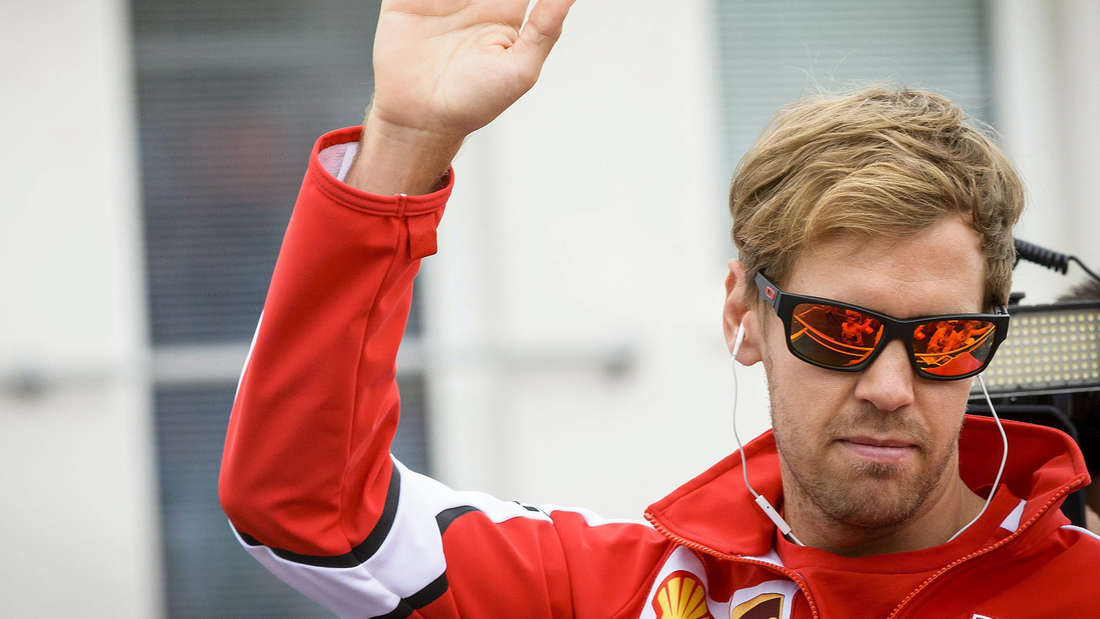 Ferrari-Pilot Sebastian Vettel winkt seinen Fans zu.