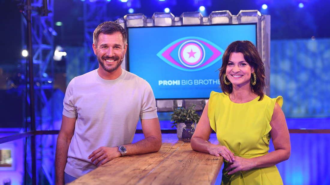 Jochen Schropp und Marlene Lufen stehen an einem Tisch, dahinter das Logo von Promi Big Brother.