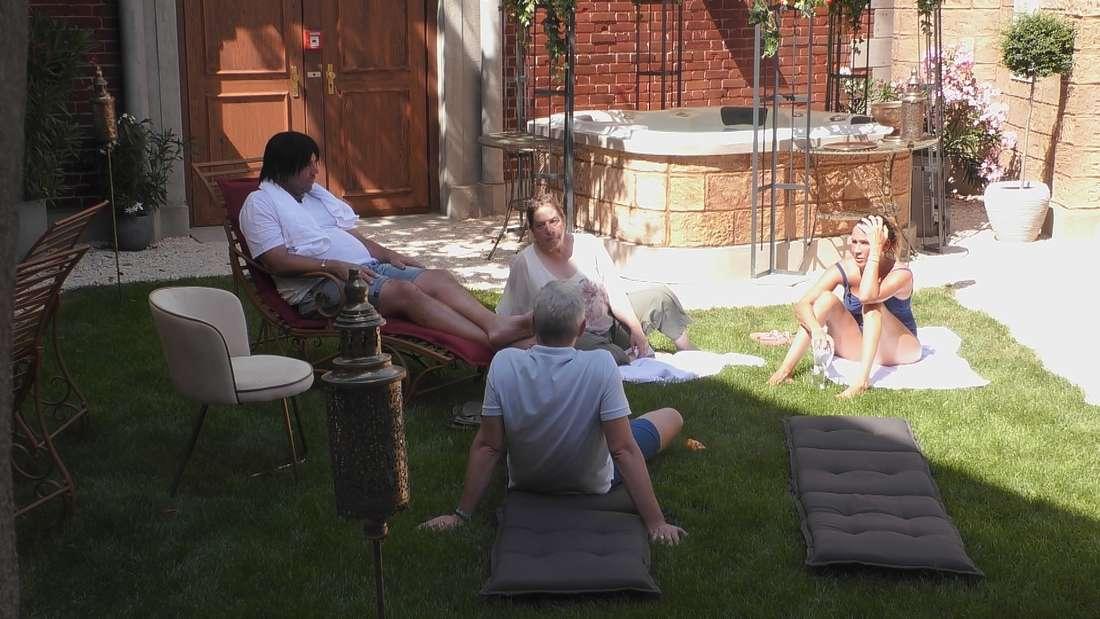 Vier Bewohner auf dem Rasen.