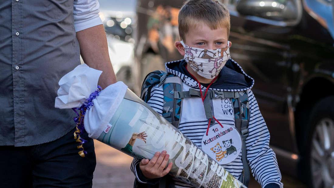 Ein Junge auf dem Weg zur Einschulung in Niedersachsen. Er trägt eine Schutzmaske aufgrund der Beschränkungsmaßnahmen wegen Covid-19