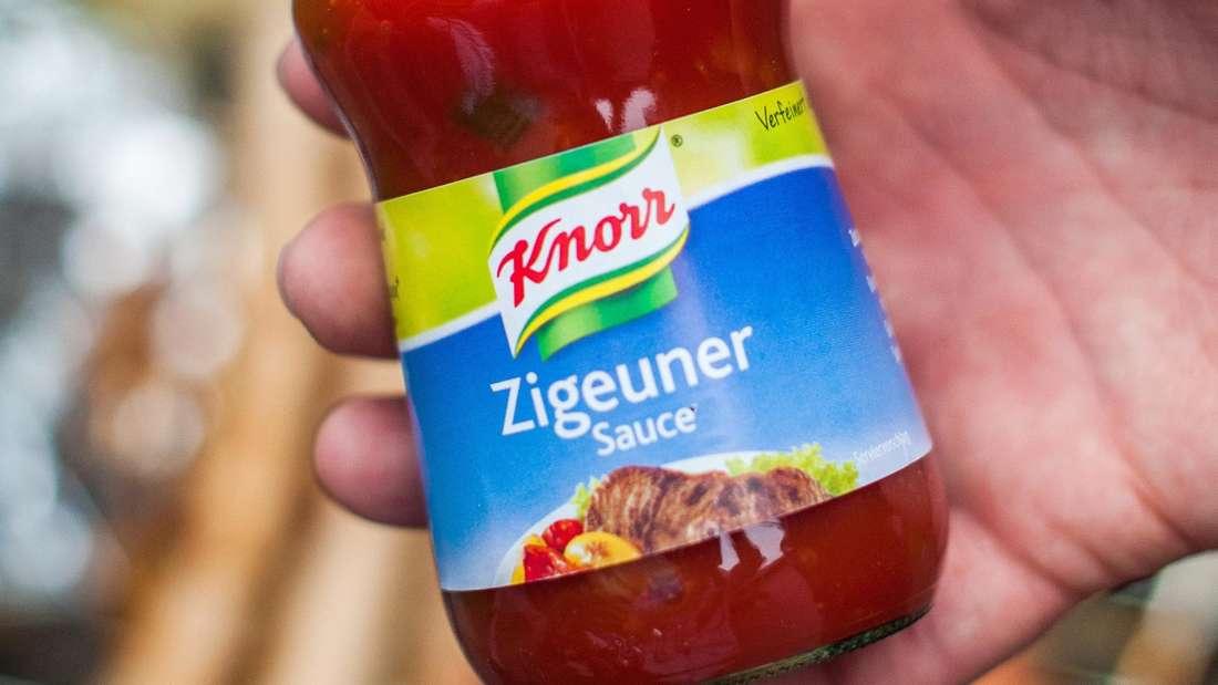 """Ein Mann hält eine Flasche """"Zigeunersauce"""" des Herstellers Knorr in der Hand."""
