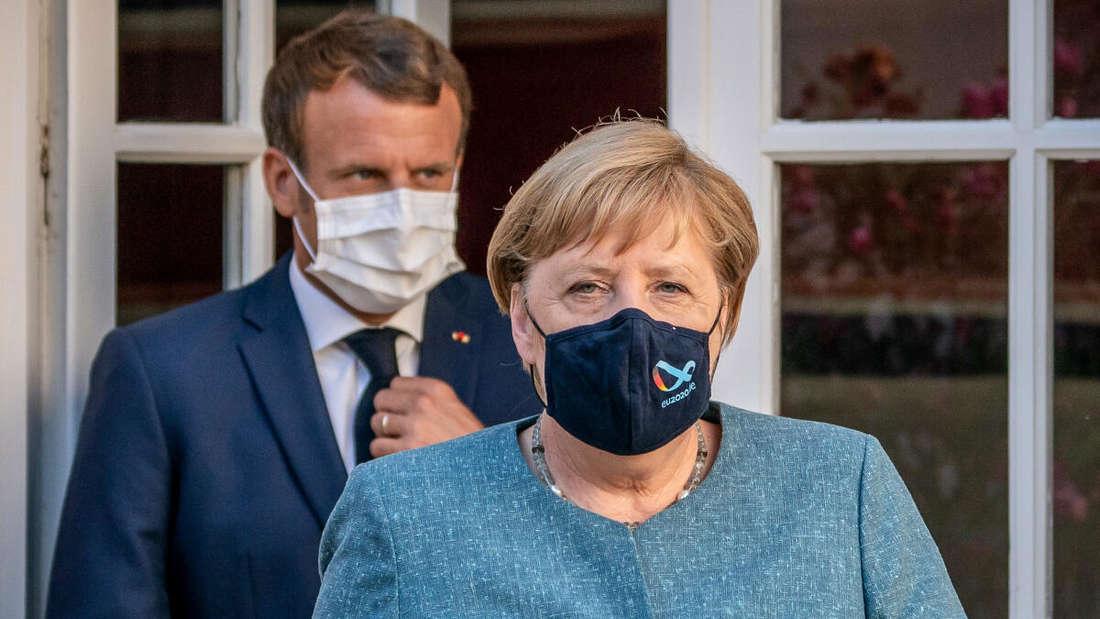 Emmanuel Macron und Angela Merkel stehen mit Masken vor einer Tür.