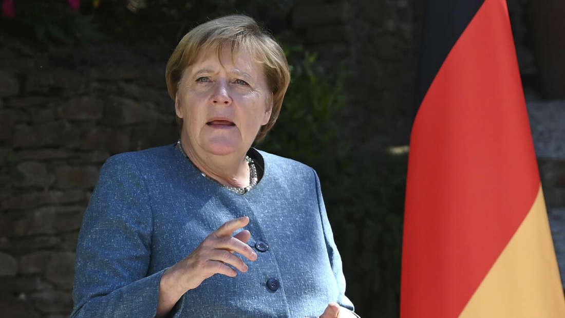 Bundeskanzlerin Angela Merkel (CDU) steht vor einer Deutschland-Flagge und spricht. (Archivbild)