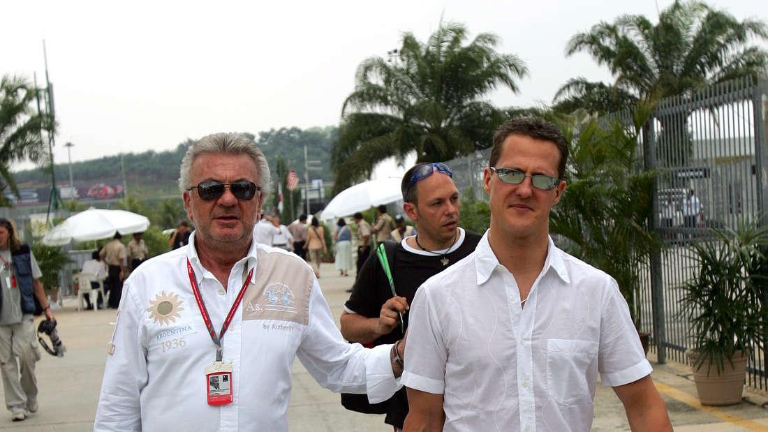 Michael Schumacher läuft mit seinem Manager Willi Weber.