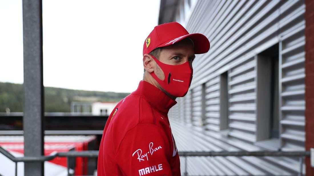 Sebastian Vettel steht in Ferrari-Rot und mit Mundschutz am Motorhome in Spa-Francorchamps.