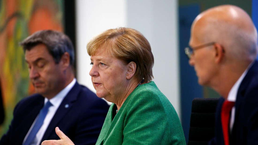 Bundeskanzlerin Angela Merkel (CDU) sitzt mit dem bayerischen Ministerpräsidenten Markus Söder (CSU, l) und Hamburgs Erstem Bürgermeister, Peter Tschentscher (SPD), bei einer Pressekonferenz im Kanzleramt.