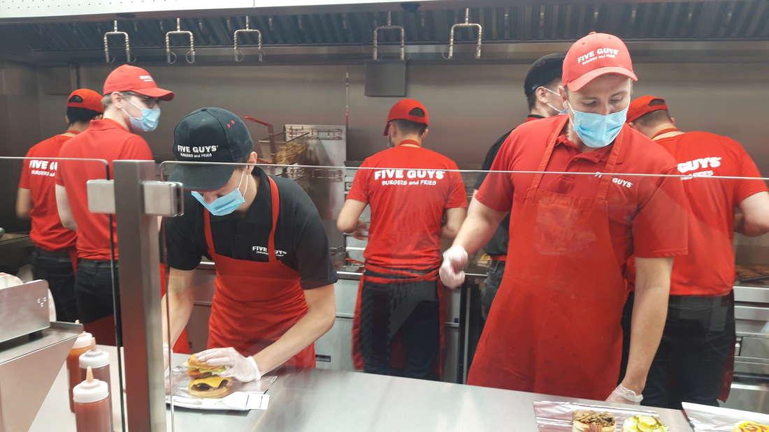 Mehrere Personen machen Hamburger.