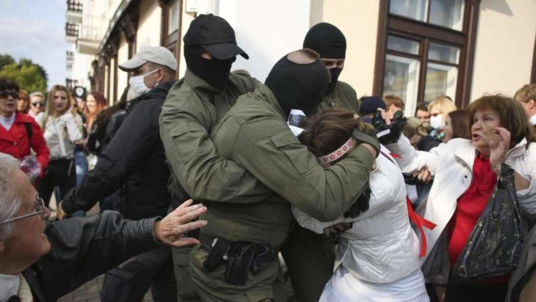 Eine Frau wird von zwei vermummten Männern brutal nach unten gedrückt, eine andere im Hintergrund sieht entsetzt aus - sie ist elegant gekleidet und mittleren Alters.