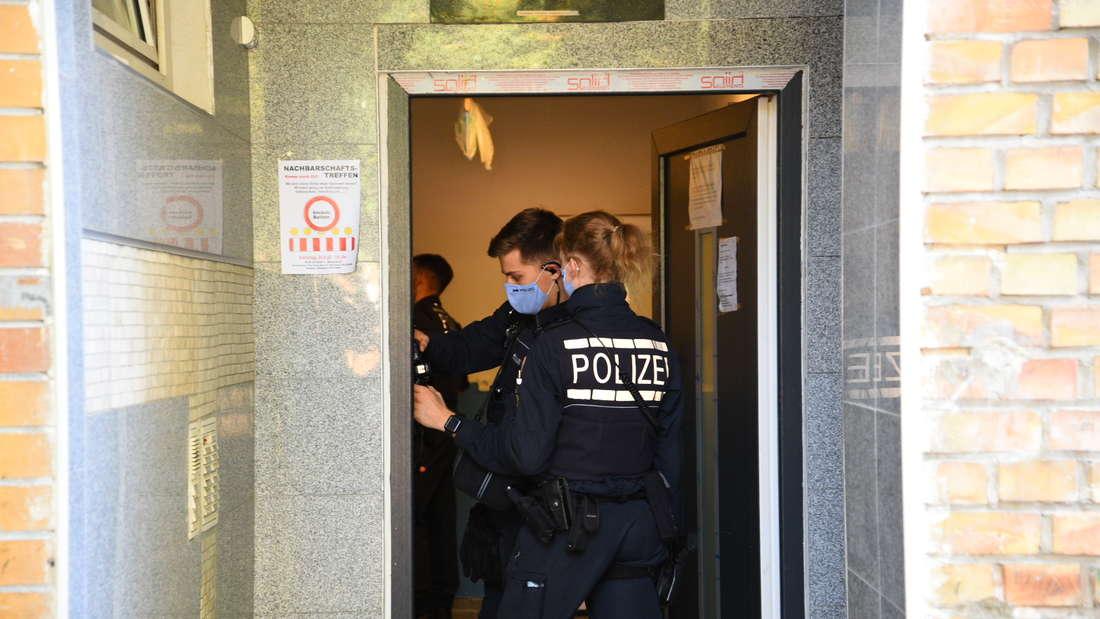 Eine Polizistin und ein Polizist stehen in der offenen Tür einer Wohnung.