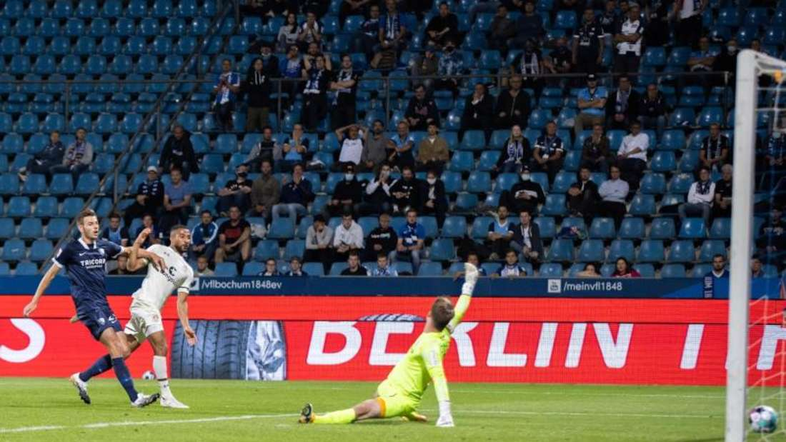 St. Paulis Daniel-Kofi Kyereh (M) schießt den Ball zum 2:2 in das Tor von Bochums Torwart Manuel Riemann (r). Foto: Marcel Kusch/dpa