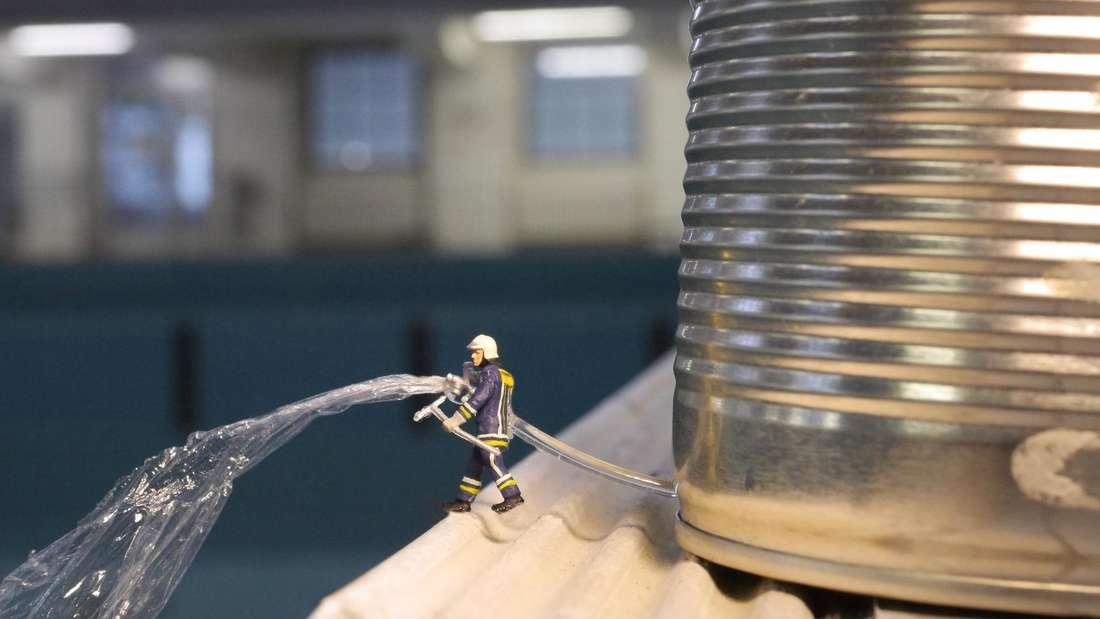 """Eine Miniatur-Figur befüllt ein Schwimmbecken mit Wasser aus einem Schlauch. Als """"Tank"""" dient eine Konservendose."""