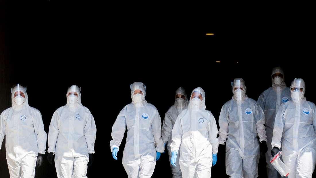 Medizinisches Personl trägt Schutzkleidung bei der Eröffnung eines mobilen Corona-Testzentrums