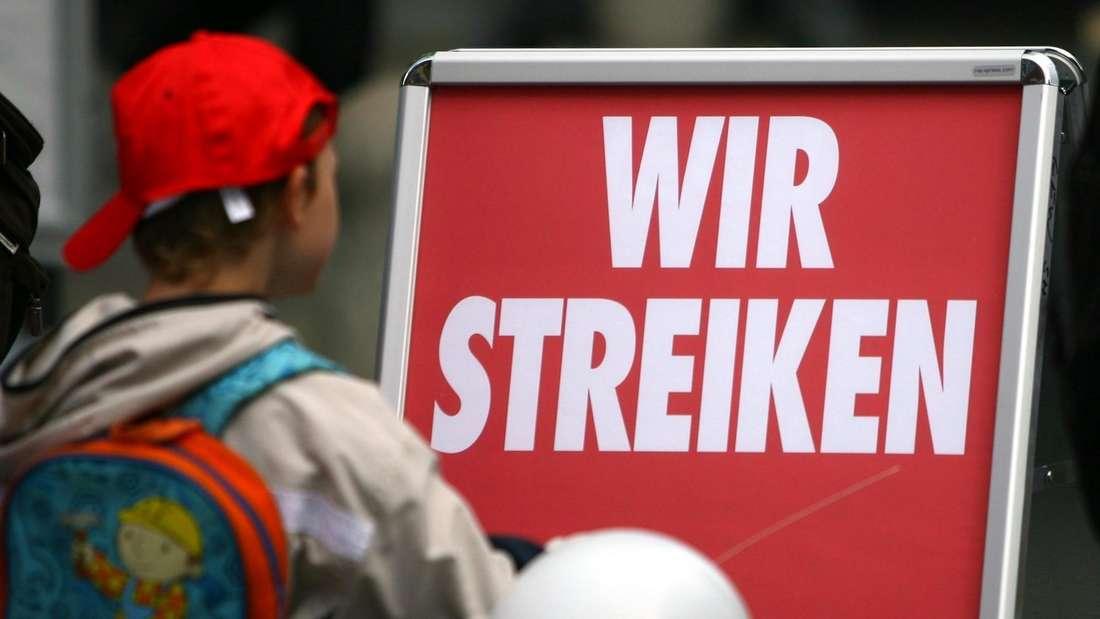 Ein Kind steht vor einem Schild im Rahmen eines Kita-Streiks.
