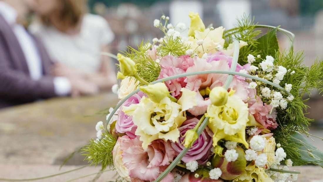 Ein frisch vermähltes Brautpaar küsst sich hinter ihrem Blumenstrauß und den beiden Eheringen, die auf dem Brückengeländer liegen.