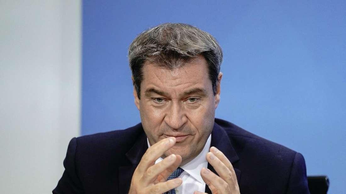 Bayerns Ministerpräsident Markus Söder (CSU) hält auf einer Pressekonferenz die Hände über den Tisch.