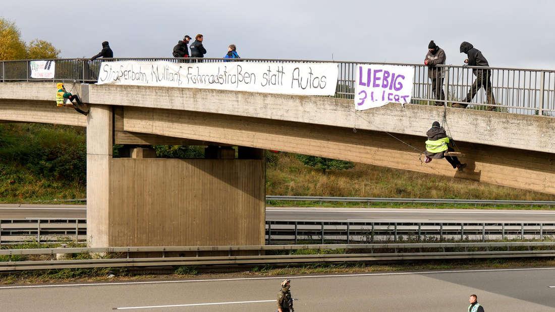 Umweltaktivisten hängen am 13. Oktober an einer Brücke über der A3