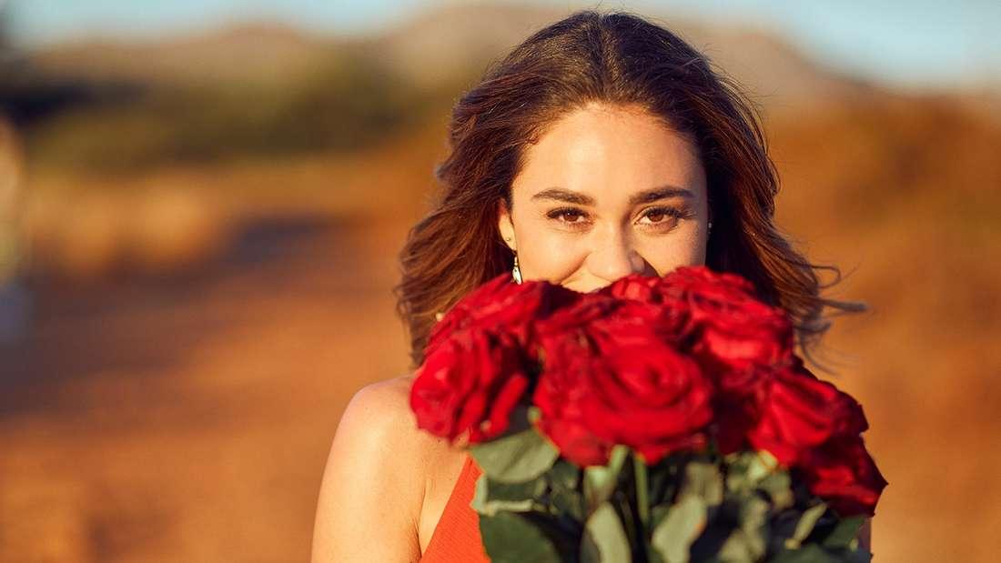 Bachelortte Melissa versteckt sich hinter einem großen Strauß rote Rosen, den sie verteilen soll.