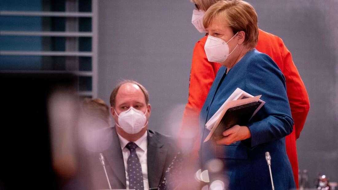 Bundeskanzlerin Angela Merkel und Helge Braun (beide CDU), Chef des Bundeskanzleramtes und Bundesminister für besondere Aufgaben, nehmen mit einer Mund-Nasenbedeckung an der Sitzung des Bundeskabinetts im Bundeskanzleramt teil.