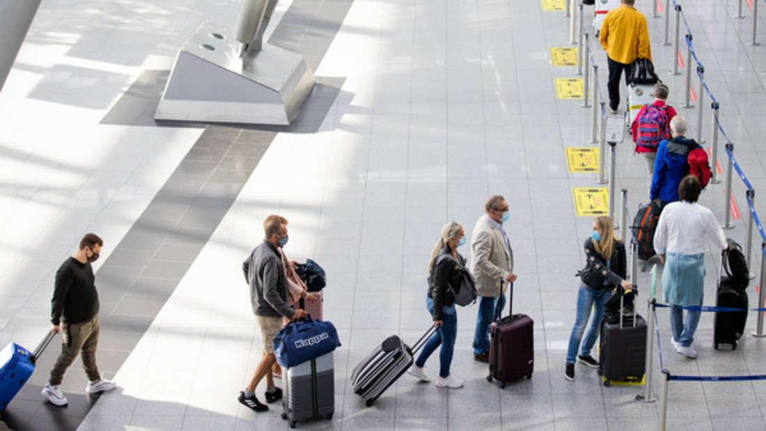 Reisende warten vor einem Check In Schalter am Flughafen.