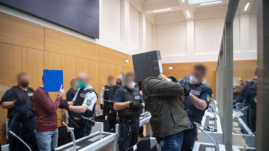 """Die Angeklagten werden von Justizbeamten kurz vor Beginn des Prozesses gegen die rechtsterroristische """"Guppe S"""" in einem Saal im Oberlandesgericht Stuttgart-Stammheim geführt."""