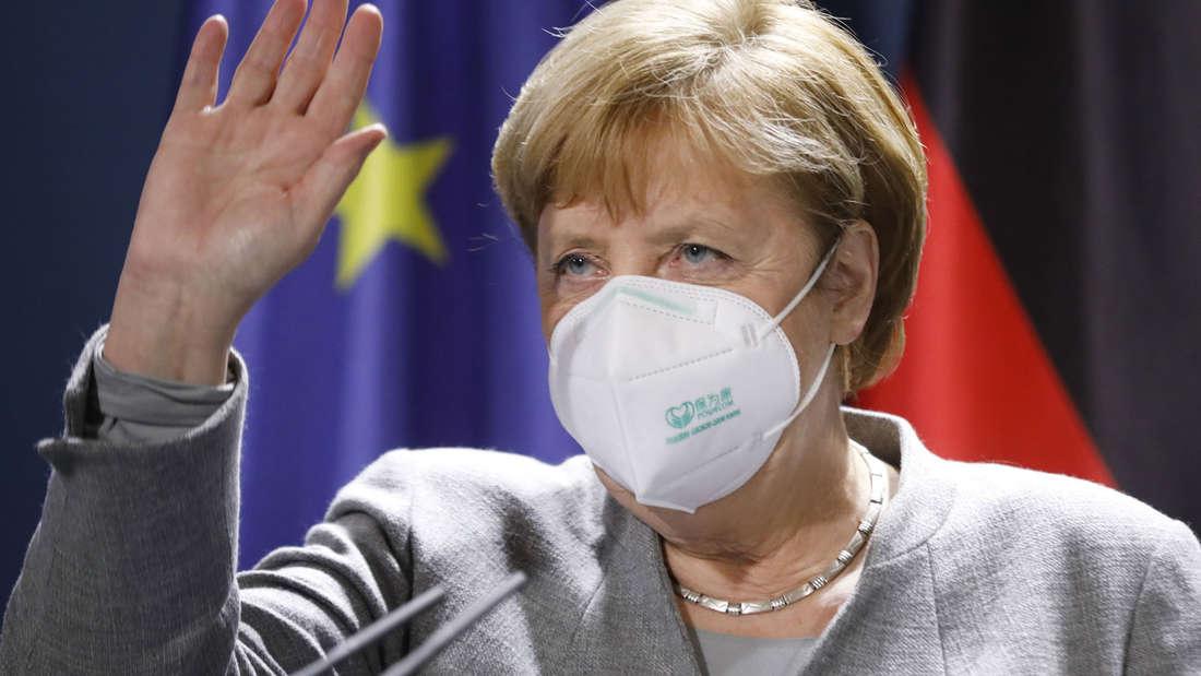 Bundeskanzlerin Angela Merkel (CDU) winkt bei ihrer Ankunft mit einer Nase-Mund-Schutzmaske im Bundeskanzleramt in Berlin.