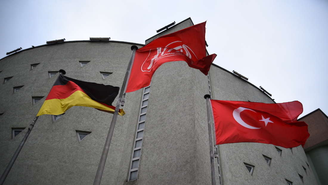Graues Steingebäude (Moschee) von außen mit Deutscher und Türkischer Flagge