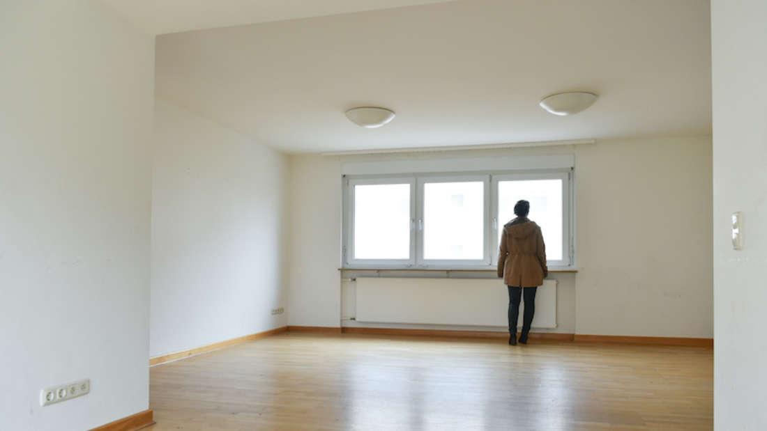 Eine Frau steht in einer leeren Wohnung am Fenster und schaut hinaus.