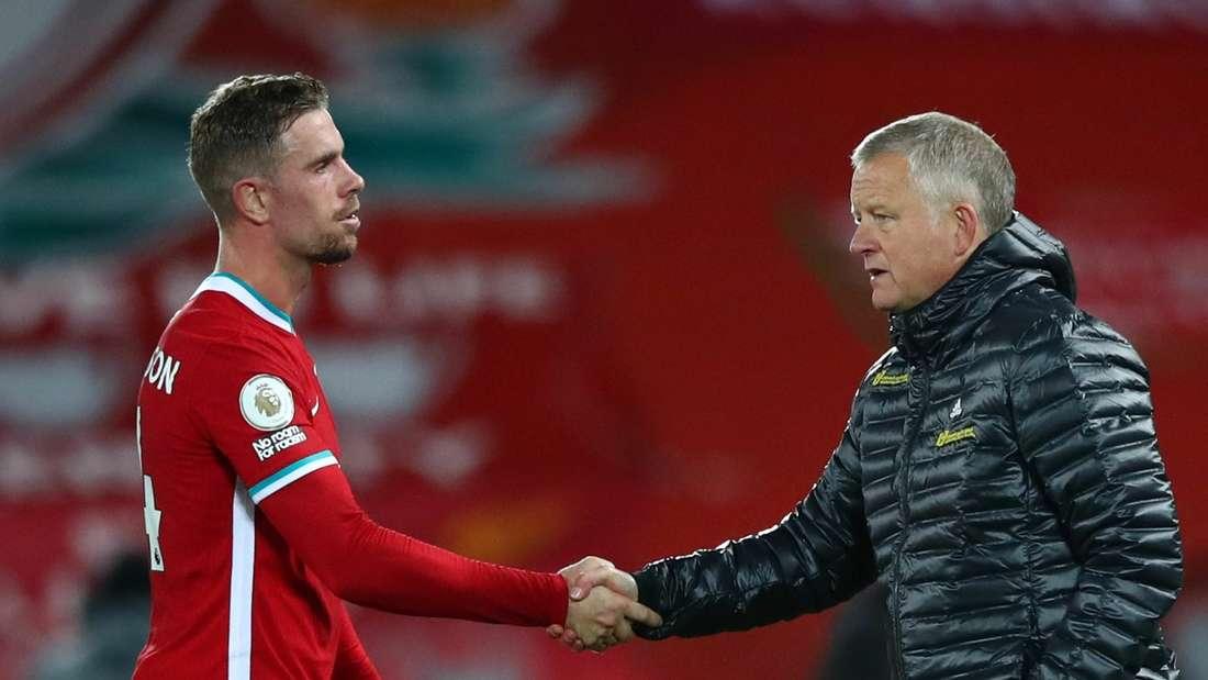 Sheffields Coach Chris Wilder (r.) reicht Liverpools Kapitän Jordan Henderson die Hand.