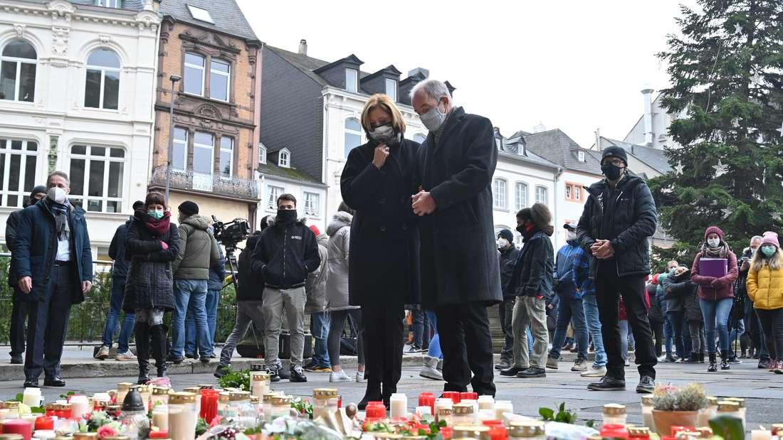 Malu Dreyer, Ministerpräsidentin von Rheinland-Pfalz, und ihr Ehemann Klaus Jensen stehen vor Blumen und Kerzen, die vor der Porta Nigra niedergelegt wurden.