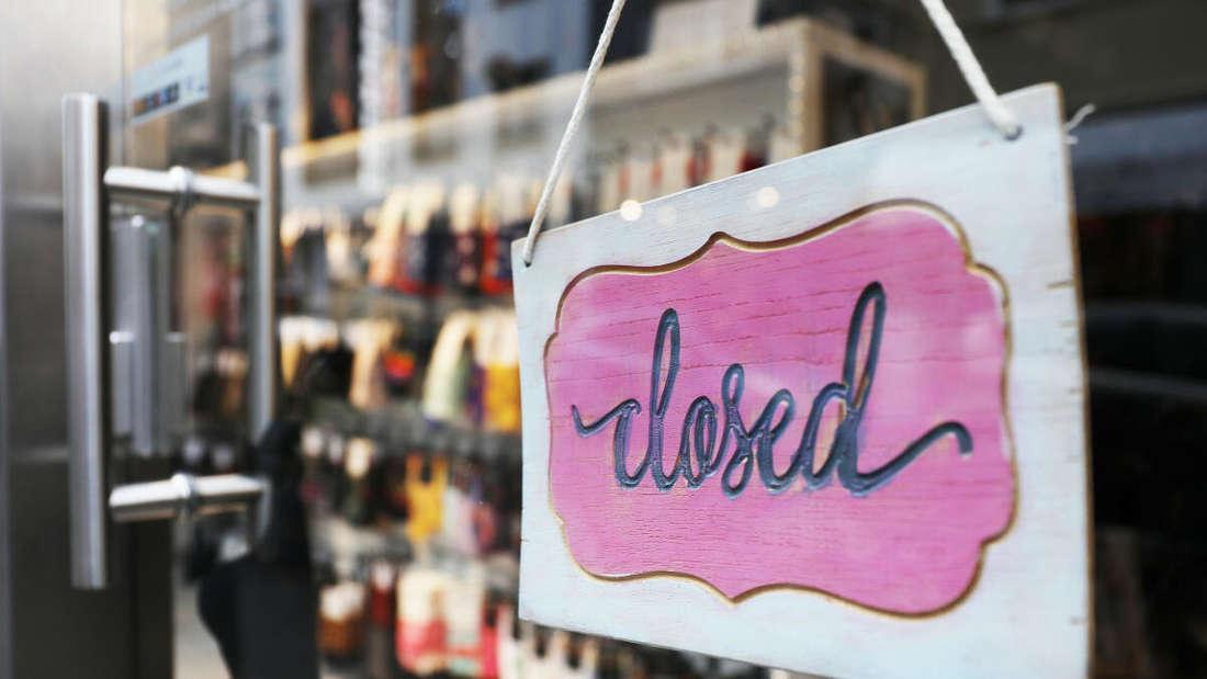 """Das Schild """"closed"""" hängt in der Tür eines Geschäftes."""