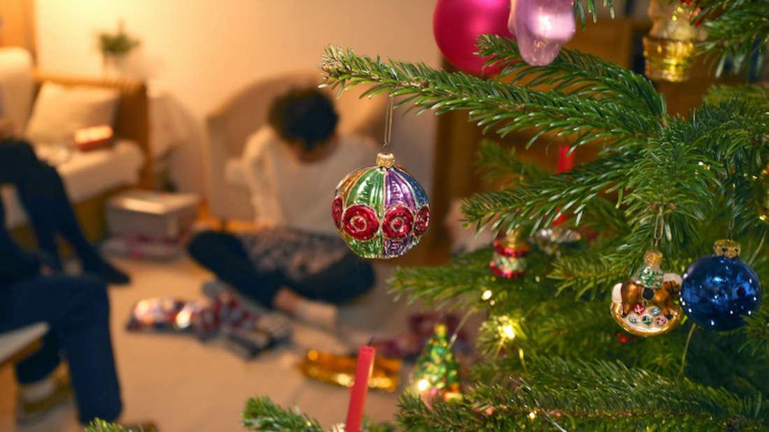 Eine Familie packt hinter einem geschmücktem Christbaum Weihnachtsgeschenke aus.