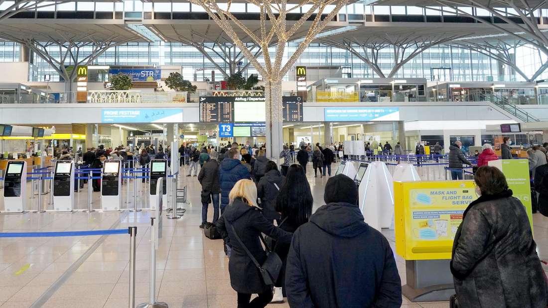 Menschen stehen Schlange am Flughafen Stuttgart.