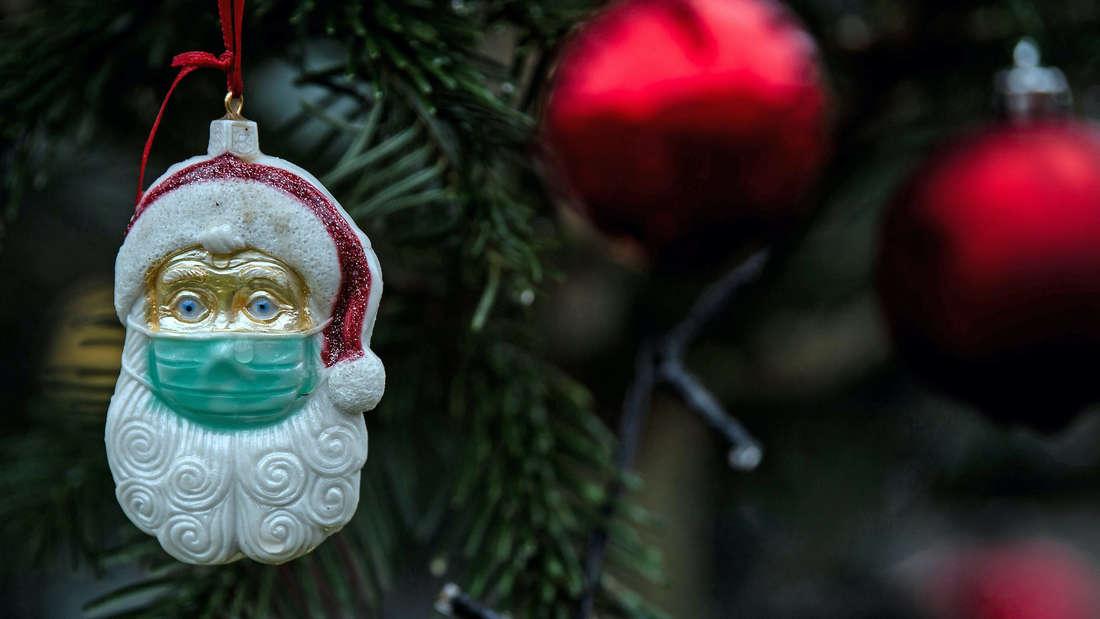 Ein Weihnachtsmann mit Mundschutz an einem Weihnachtsbaum.