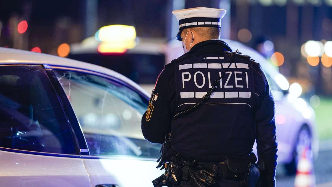 Ein Polizist kontrolliert ein Auto.
