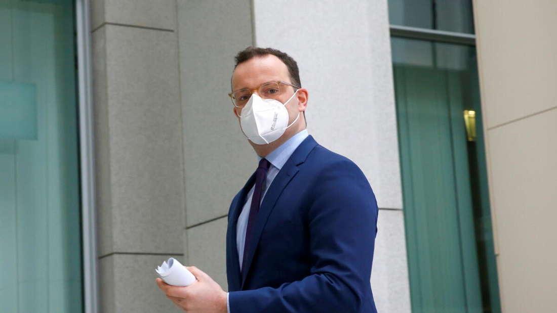 Bundesgesundheitsminister Jens Spahn (CDU) blickt mit FFP2-Maske und einem Zettel in der Hand in die Kamera.