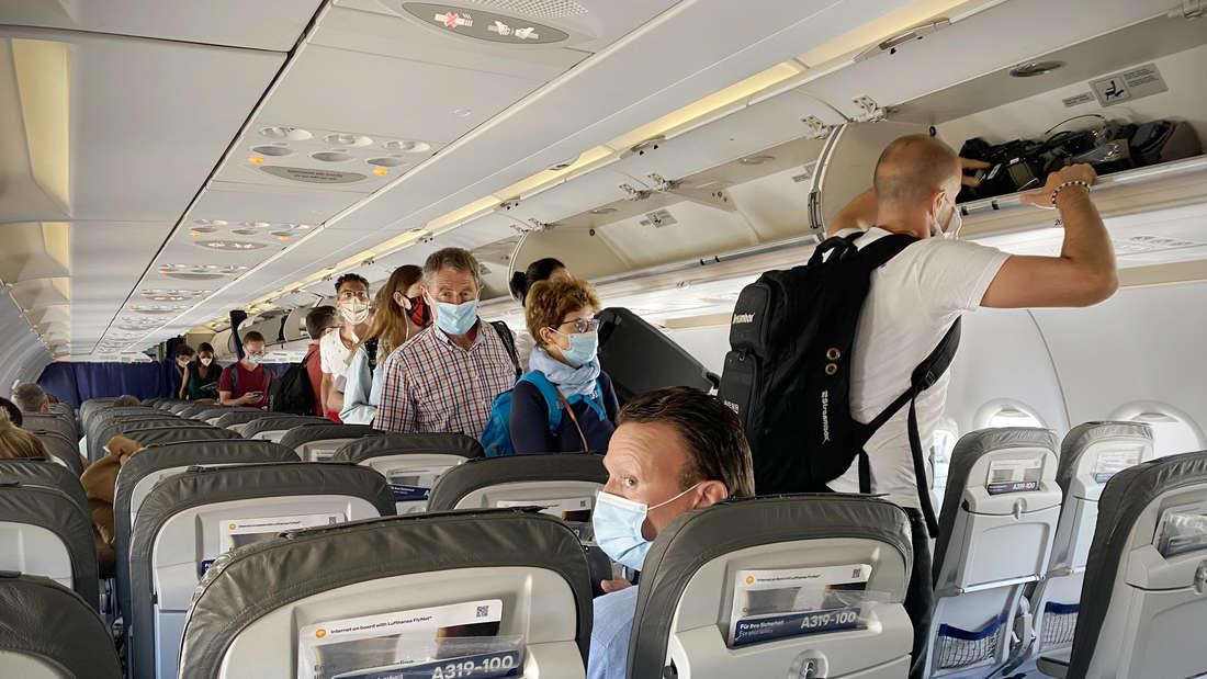 Fliegen in Zeiten der Coronavirus Pandemie, Passagiere tragen Mundschutz, Maske