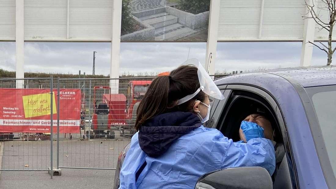 Eine Mitarbeiterin nimmt einen Nasenabstrich im Schnelltestcenter auf dem Bauhaus-Parkplatz in der Eppelheimer Straße in Heidelberg.