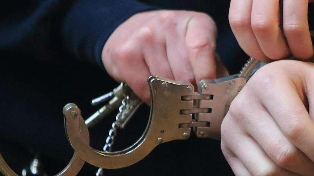 Einem Mann werden Handschellen angelegt (Symbolfoto).
