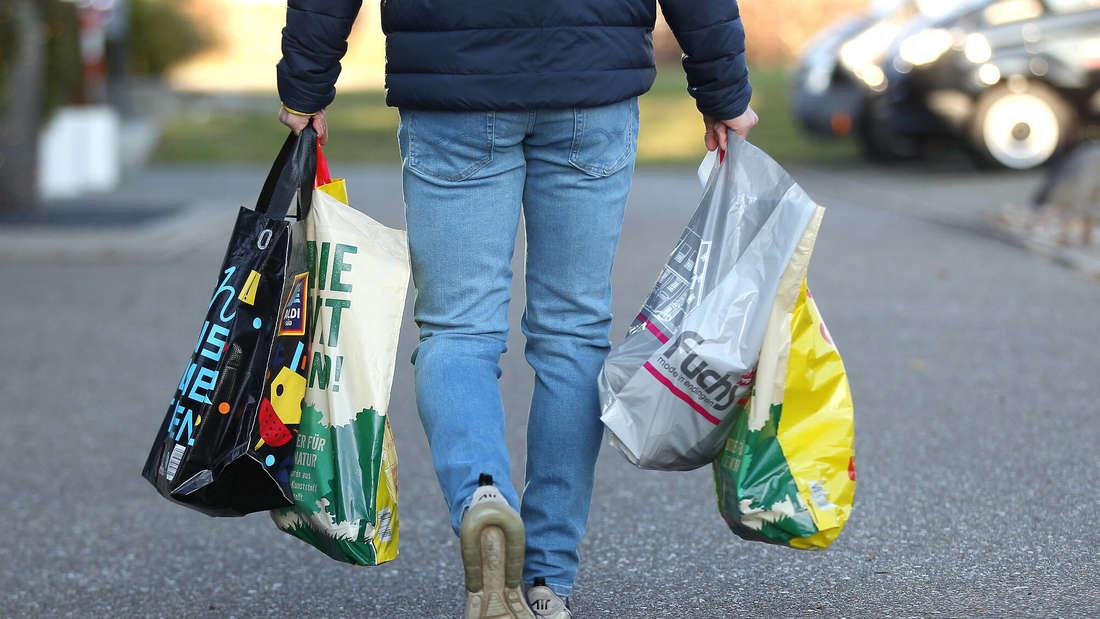 Ein Mann trägt mehrere Einkaufstüten von Aldi und Netto.